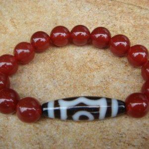 Armband met 3-ogige Dzikraal en rode jasperkraaltjes